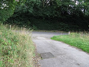 English: Junction of footpath with a busy B ro...