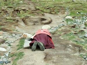 Kora (pilgrimage) - A pilgrim circumambulating Mt. Kailash by performing full body prostrations.