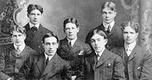 Seven men apparently in their 20s pose for a half-length group photo. They are wearing formal suits and ties.