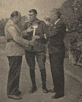 Antonin Magne en uniforme entre deux journalistes en civil, qui lui tendent une louche.