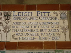 "Almost identical to the plaque to Amelia Kennedy, a tablet formed of five tiles of varying sizes, bordered by yellow and blue flowers in an art nouveau style and decorated by two stylised salmon. The tablet reads ""Leigh Pitt, reprographic operator, aged 30, saved a drowning boy from the canal at Thamesmead, but sadly was unable to save himself June 7, 2007""."