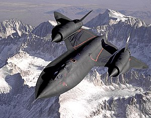 Dryden's SR-71B Blackbird, NASA 831, slices athort the snaw-covered soothren Sierra Nevada Muntains o Californie efter bein refueled bi an Air Force tanker durin a 1994 flight. SR-71B wis the trainer version o the SR-71. The dual cockpit tae allae the instructor tae flee. Note the streaks o fuel frae refuelin spillage.