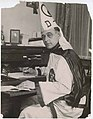 Luther Powell sitting at desk in Klan robes, circa 1923 (MOHAI 15393).jpg