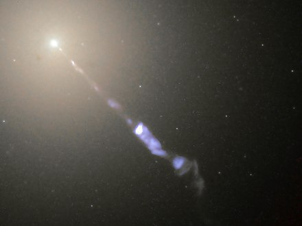 Figure 5-5. Galaxy M87 streams out a black-hole-powered jet of electrons and other sub-atomic particles traveling at nearly the speed of light. M87 jet (1).jpg