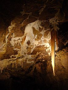 A long stalactite hangs from the ceiling of a cave passage, with some smaller calcite stalactites nearby.