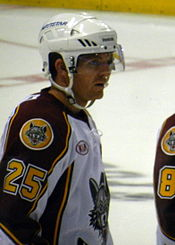 A Caucasian ice hockey player shown from the waist up. He wears a white helmet with a visor and a white jersey with maroon shoulders and sleeves. The number 25 is on his sleeve in yellow below a patch with the Wolves' logo.
