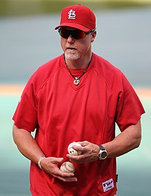A man in a red athletic shirt holds a baseball in each hand. He is wearing a red cap and sunglasses.