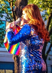 Meghan Trainor performing on stage with a rainbow flag
