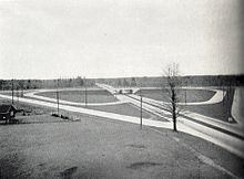 """A black and white photograph of a divided roadway being crossed by another roadway. The horizon cuts the photo in half. The setting is mostly rural, with the roadways slicing through that. The divided road extends from the lower right corner to the centre of the horizon, while the second roadway crosses horizontally halfway towards the foreground. Connecting the two separated roadways are a series of ramps. Although only half visible from the angle of the photo, the ramps form the shape of a four-leaf clover surrounded by a diamond."""