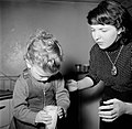 Moeder helpt haar peuter bij het op tafel zetten van een glas melk, Bestanddeelnr 252-9380.jpg