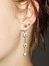 A Navel Curve Used As An Earring With Green Gemmed Ear Stud Above It