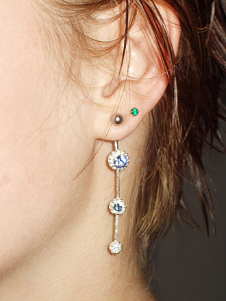 Earring - A navel curve used as an earring with a green gemmed ear stud above it