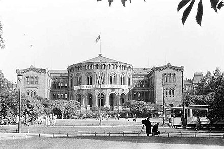 The Parliament of Norway Building in 1941, with the Swastika flag flying and a Nazi slogan across the front of the building reading Deutschland siegt an allen Fronten Nazi-occupied Parliament of Norway 1941.jpg