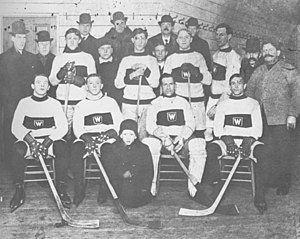 rows of men in hockey uniforms, some men wearing overcoats and hats