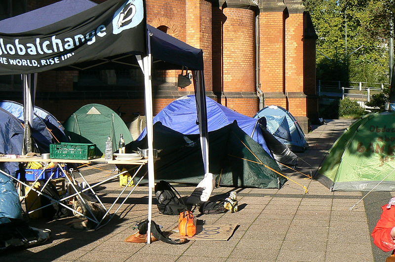 Kirchenvorplatz mit Zelten und einem Pavillon, an dem ein Banner der Occupy-Bewegung angebracht ist
