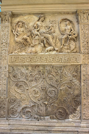 """Scroll (art) - The """"Tellus Panel"""" from the Ara Pacis, Rome, c. 27 AD. A speading scrollwork panel below, scrolling forms coming off a straight stem in the side panels, and a border band of meanders below the figures."""
