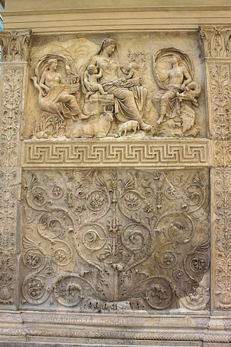 "Scroll (art) - The ""Tellus Panel"" from the Ara Pacis, Rome, c. 27 AD. A speading scrollwork panel below, scrolling forms coming off a straight stem in the side panels, and a border band of meanders below the figures."