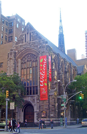 "A tall brown stone church with a pointed roof and spire in the rear in an urban area. A red banner with ""Welcome to the Park"" written on it hangs from the front. On the ground in front is an intersection with a traffic light."