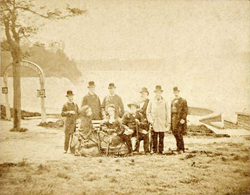 Photograph of three people, two women and a bearded man, seated on a park bench with six other men standing in back and waterfalls in the distance