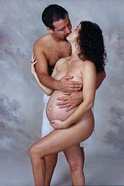 Couple hétérosexuel s'embrassant, la femme étant enceinte