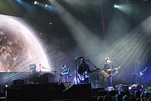 A stage shot of six men performing: From left, a man seated at keyboards with a microphone, the drummer behind his kit with a drumstick raised in his right hand, a guitarist singing into a microphone, another singer-guitarist highlighted by overhead lighting, a man playing a bass guitar who is mostly obscured behind the lead singer, and the last man at right who is also playing a guitar. In front of the stage are cameramen and audience members. Above is further stage lighting with, at left, a large projected image of the top part of the moon.
