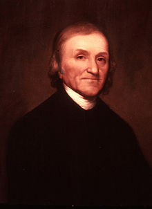 Half-length portrait of an older man. He is wearing a black jacket with the white collar of his shirt showing.