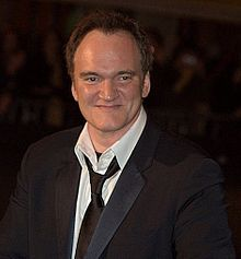Quentin Tarantino in a suit, smiling