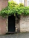 Natuurstenen poortje met geprofileerde korfboog op kraagsteen