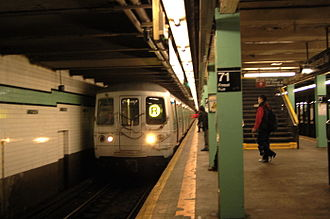 Forest Hills–71st Avenue (IND Queens Boulevard Line) - A Manhattan-bound R train arriving at the station.