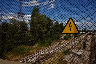 Railway electrification system - Image of a sign for high voltage above railway electrification system