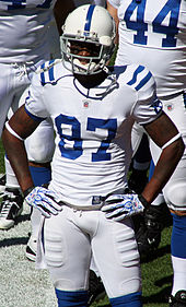 A dark-skinned man wearing a white football jersey and helmet
