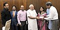 Renowned cricketer and Chairperson of Khushii (Kinship for Humanitarian Social and Holistic Intervention in India), Shri Kapil Dev presenting a cheque of Rs. 51 lakhs to the Prime Minister, Shri Narendra Modi.jpg