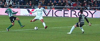 Brazilian striker Ronaldo taking a shot at goal. A multi-functional forward, he has influenced a generation of strikers who followed. Ronaldo Real Madrid.jpg