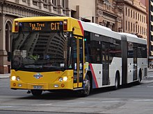 Photo of yellow and white articulated bus