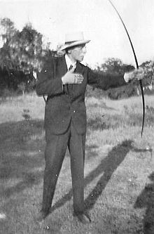 A black and white photograph showing an older man in a dark suit and tie, wearing a panama hat, with glasses and a light-coloured moustache. He is using a bow, his body is facing towards the camera, while he looks to the right, aiming the bow in the same direction. He is standing on grass, with shrubs and trees in the background.