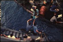 Un homme vietnamien tend un enfant à des membres d'équipage américains en attente