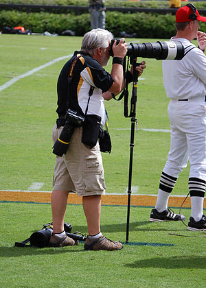 Sports photography - Photographer on the sideline of an American football game with multiple cameras, long lenses, and monopods.