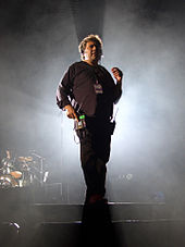 A man in a black shirt and pants standing on a smoky stage.