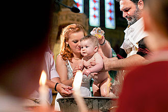Infant baptism - Christening photograph showing the oil moment and Baptism in Greek Orthodox Church.