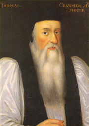Portrait of Archbishop Cranmer as an elderly man. He has a long face with a flowing white beard, large nose, dark eyes and and rosy cheeks. He wears clerical robes with a black mantle over full white sleeves and has a doctoral cap on his head