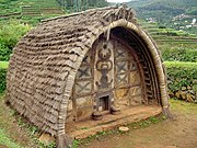 An oval-roofed hut of the Toda people of the Nilgiris. The walls are made of dressed stone and decorated with mural painting