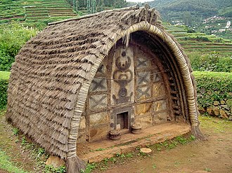 Toda people - The hut of a Toda Tribe of Nilgiris, India. Note the decoration of the front wall, and the very small door.