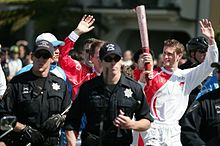 Torchbearer Trevor Robinson carrying the Olympic Torch near Golden Gate Park with the Flame Attendants in blue and SFPD in black.jpg