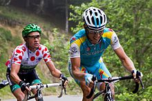 Thomas Voeckler wearing a white jersey with red polka dots, following Fredrik Kessiakoff as they ride up an incline
