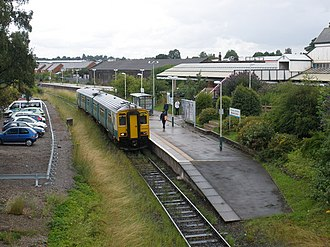 Wrexham General railway station - Wrexham Exchange site in 2009. One platform remains in use, the other as a staff car park. Wrexham General is to the right.
