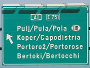 Traffic sign near Koper Slovenia. The city of Pula (in Croatia) is written in Slovene and Italian (official languages of the region) and in Croatian (official language of Croatia)