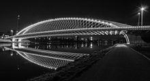 Un pont moderne sans piles, illuminé de nuit.