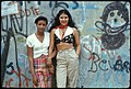 Two girls pose in front of a wall of graffiti in Lynch Park in Brooklyn, N.Y., in June 1974.jpg