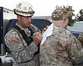 U.S. Army Staff Sgt. Kenneth Perry, left, with the 63rd Civil Support Team, Oklahoma Army National Guard, checks a personnel roster before search and rescue operations May 21, 2013, in Moore, Okla 130521-Z-BB392-303.jpg