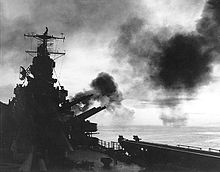 Large naval guns firing on board a ship cast in silhouette